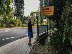 "A man standing next to the street sign ""Wetten"",Germany"