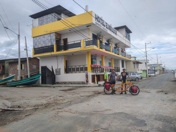 Two man holding a tandem bicycle in front if the Hotel El Mirador in Ecuador