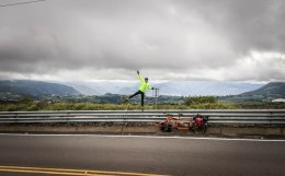 Male bicycle rider posing on a guard rail next to a tandem bicycle in Ecuador