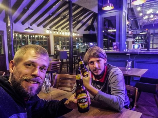 two blonde man drinking beer in a restaurant in Quito