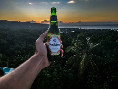 hand holding a beer in front of a tropical sunset