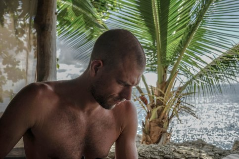 upper body shirtless bald man in front of a palm tree