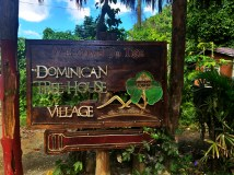 "a sign on which is written ""Dominican Treehouse Village"""