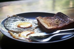 toast with two fried eggs on a plate with a fork and a knife