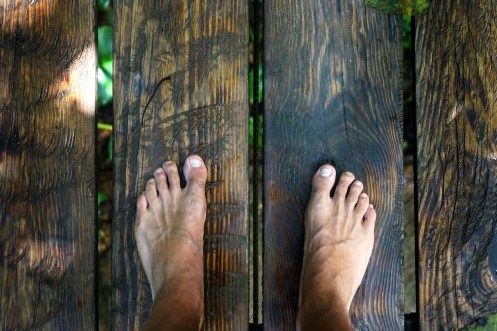 two feet standing on wooden bridge