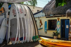 many surfboards next to a house