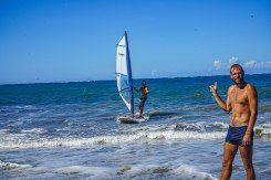 man looking at another man in the sea windsurfing