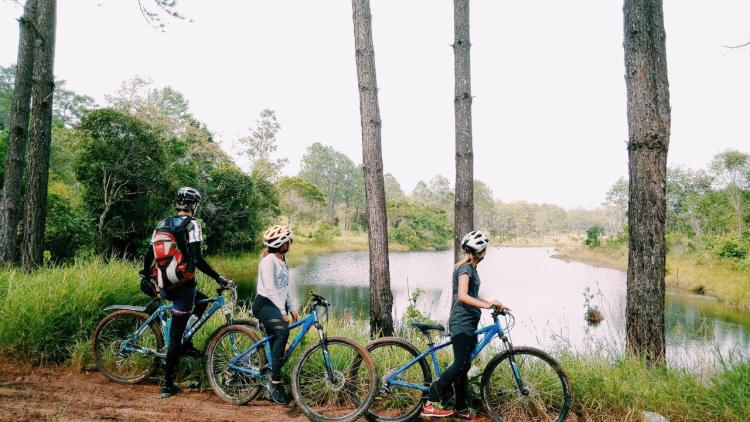 three bicycle rider stopping at a lake at Kirirom, Cambodia in Southeast Asia