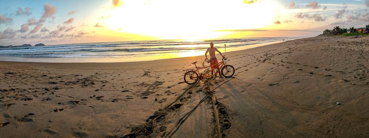 A man holding a tandem bicycle on a sandy beach during the sunset