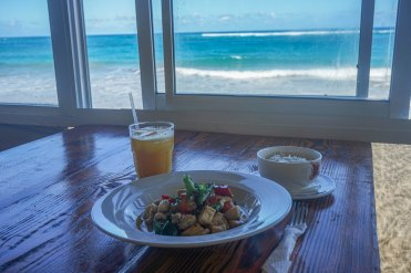 a dish with a soup and a juice on the beach