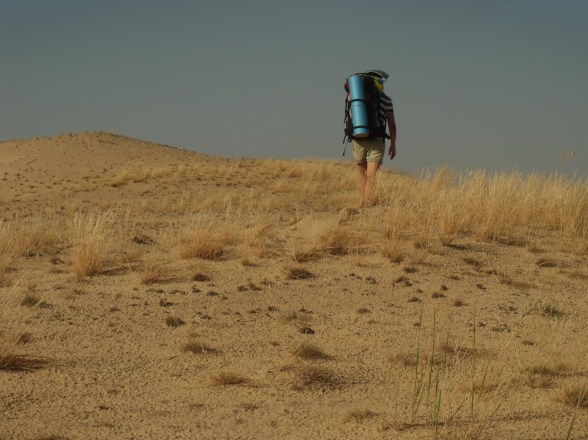 A backpacker walking through the Oleshky Sands