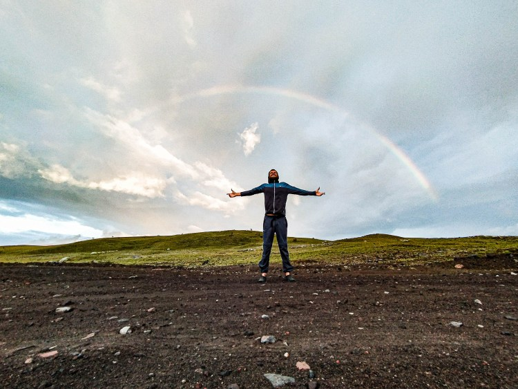 A man stretching out his arms within a rainbow circle / Hospitality Services