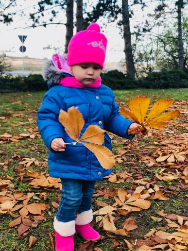 little child playing with leaves