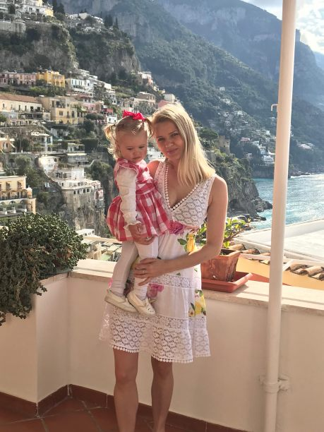 a female blonde traveler and her blonde daughter on the balcony at the sea