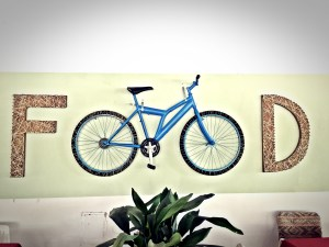 A Food sign where the doble O is a bicycle