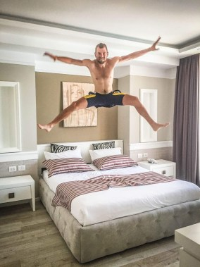 A topless blonde man jumping on a bed