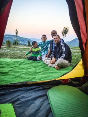 a picture out of a tent of 2 man and two kids in Albania / morning habits