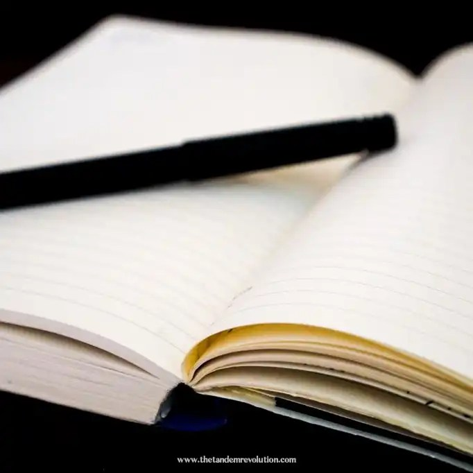 A black pen resting on white lined notebook paper.