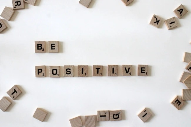 """""""Be Positive"""" spelled out in scrabble letters, with other letters scattered"""