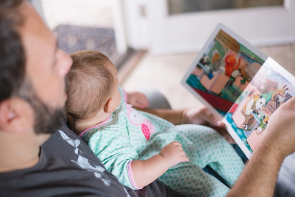 A man reading to his baby daughter on the couch.