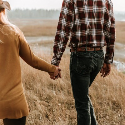 A man and a woman hold hands with their backs to the camera while walking through a field of brown grass, both attempting to be a better spouse..
