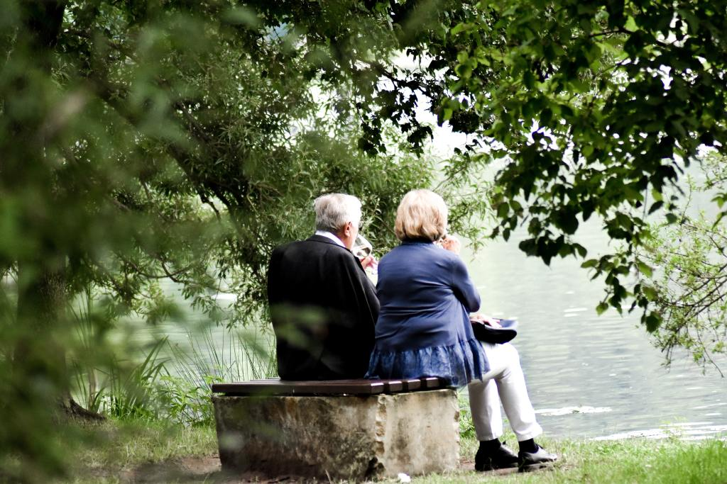 elderly couple sitting side by side on a bench