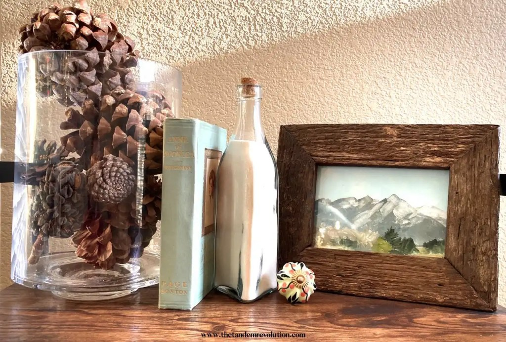 A book shelf decorated with a glass container filled with pinecones, an old book, a jar of white sand, a glass floral doorknob, and a framed mountain scene.