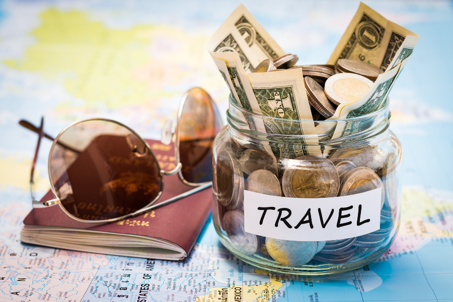 A jar filled with money, sunglasses, and a passport sit next to each other on top of a map of the world.