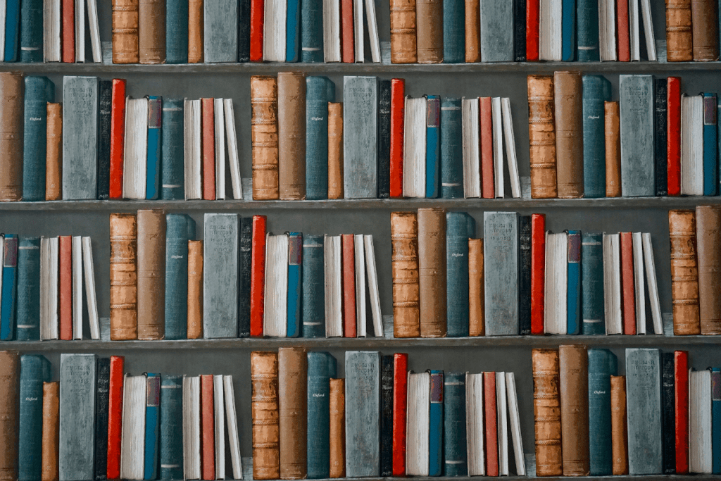 Four shelves full of antique books that show making time to read can be difficult.