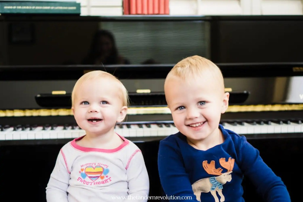 Little boy and little girl smiling sitting on a piano bench