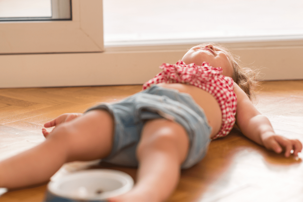 A little girl lays on the floor looking at the ceiling with her arms outstretched.