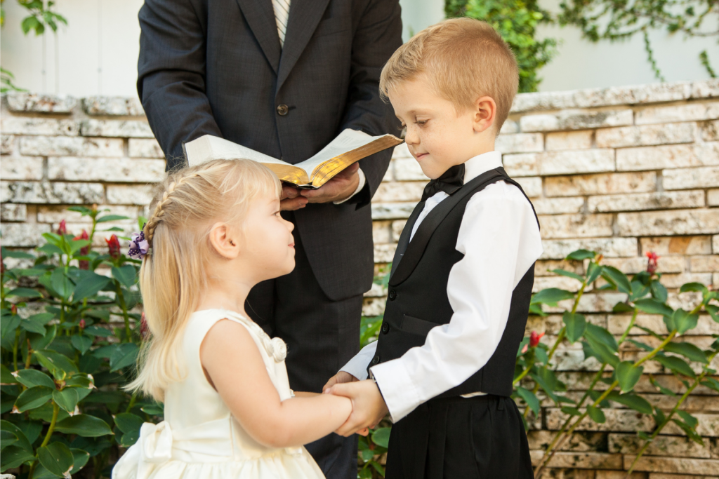 two little kids getting married in pretend, all dressed up as if for a wedding day