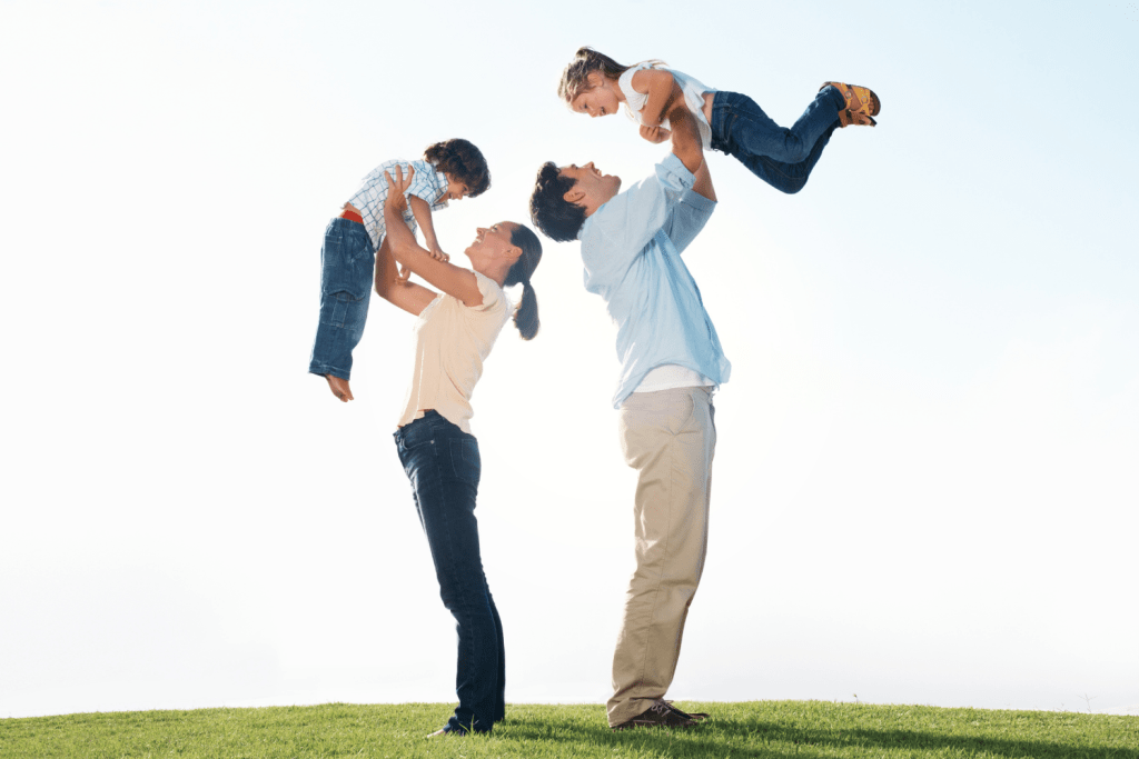 A mother and father, standing back-to-back, lift their young son and daughter into the air, neither child demonstrating a parental preference.