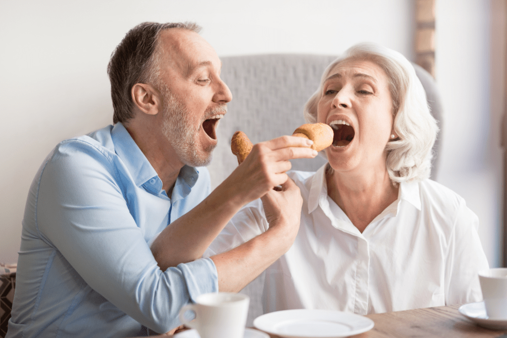 A husband and wife have fun feeding each other corn dogs.