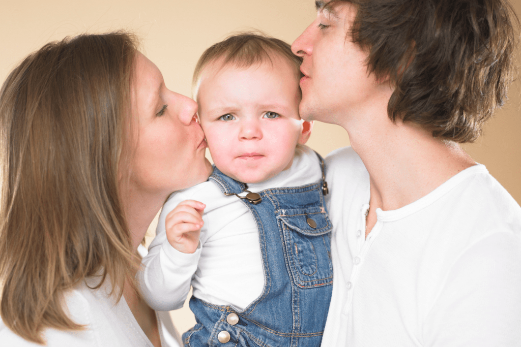 A child in overalls looks unhappily into the camera as he is kissed by both his father and his mother.