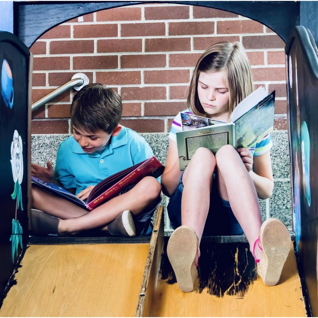A young girl and young boy reading books on slides