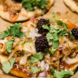 BBQ Chicken Pizza topped with blackberries, cilantro, and cheese on top of Indian naan bread