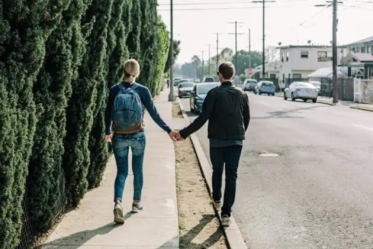 A couple walking together holding hands along a road next to a tall hedge