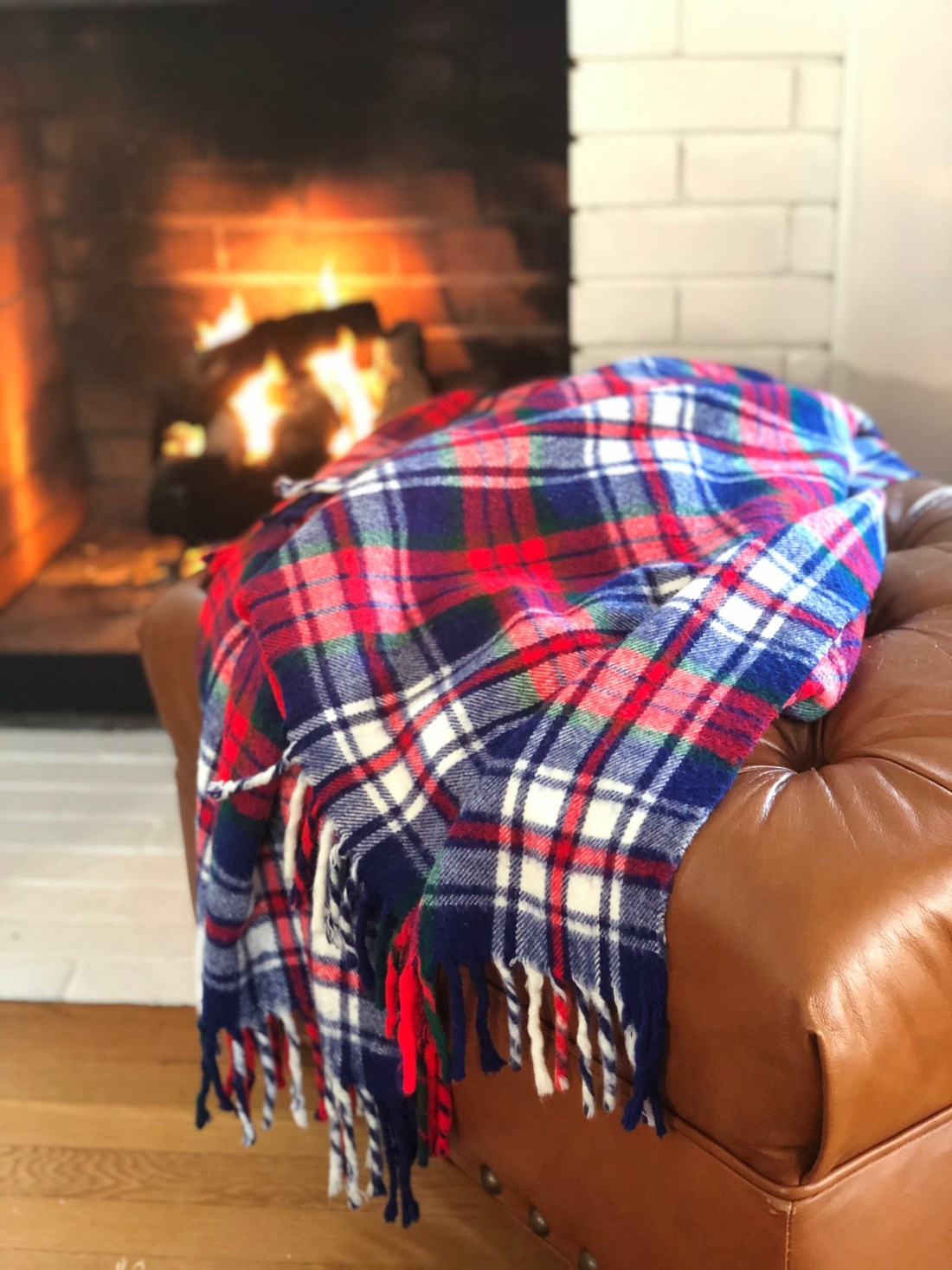 Red, green, and blue plaid blanket on leather ottoman in front of fire