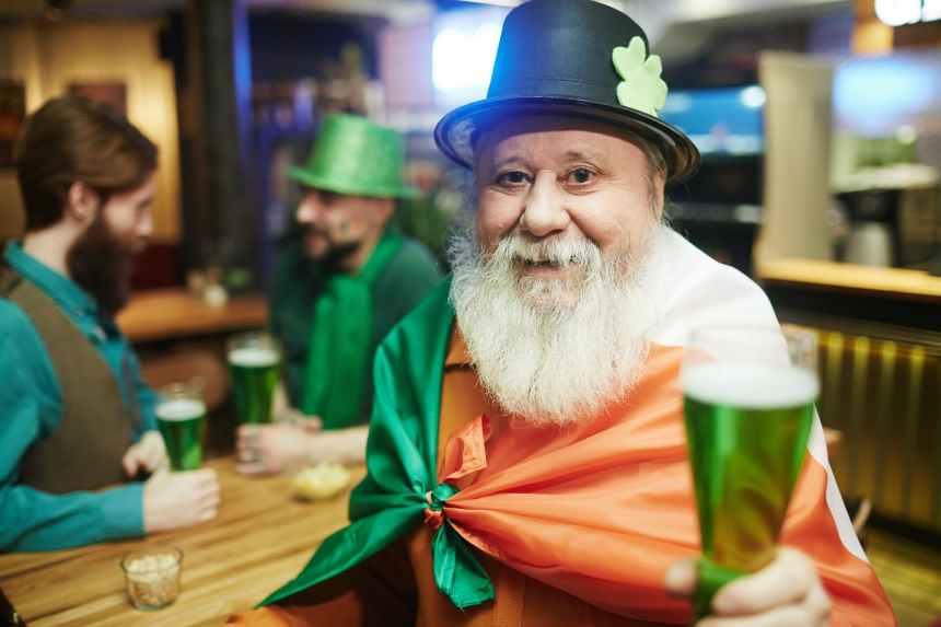 A man celebrating St. Patrick's Day in a pub.