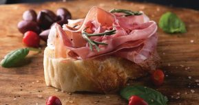 Prosciutto with bread on a wooden board