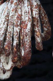 Italian Cured Sausages/Salami Hanging Against Black Background