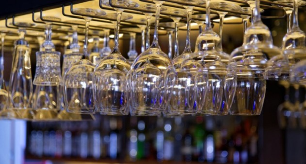 Group of empty wine glasses hanging in a bar