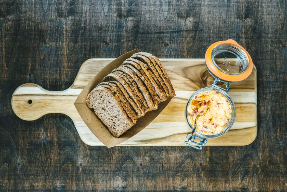 Pimento cheese dip and crackers being served on a cheese board in a weck jar.