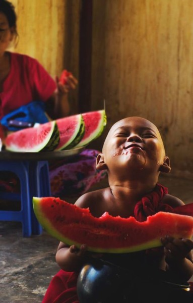 child monk eating a watermelon