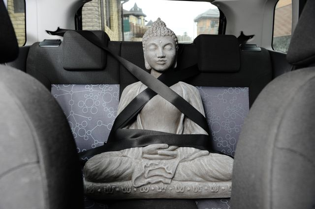 Buddha strapped in to car