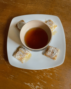 A plate with pieces of buttered toast and a cup of The Tea In Me Stone Fruit Style tea