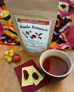 A cup of The Tea In Me Masala Romance tea, crackers with chipotle peppers, and a bag of The Tea In Me Masala Romance loose leaf tea