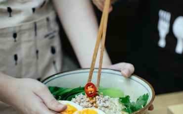 crop women with bowl of ramen