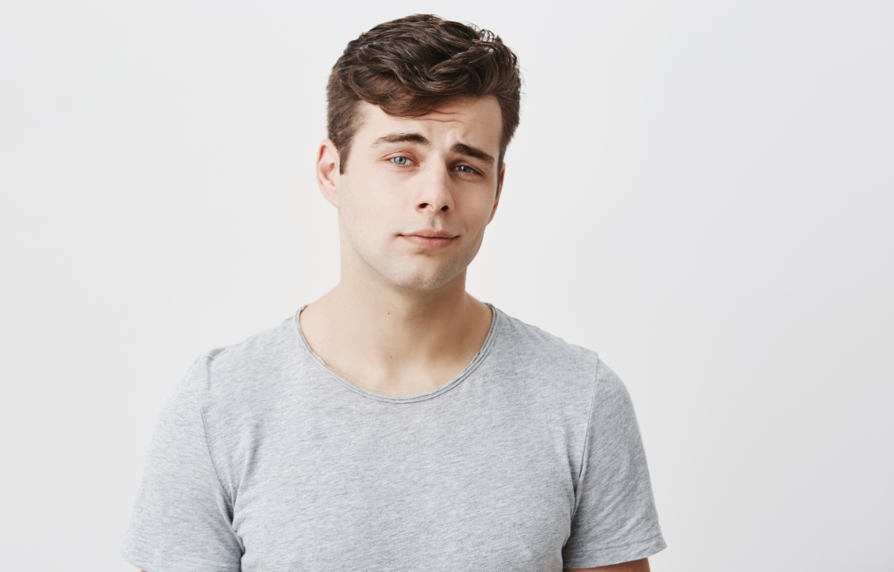 Good-looking stylish handsome male posing against gray studio wall. Attractive caucasian guy dressed casually with dark hair, looks at camera with his blue eyes, has thoughtful face expression.